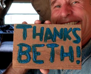 Bernie holds a sign he painted for donor Beth.