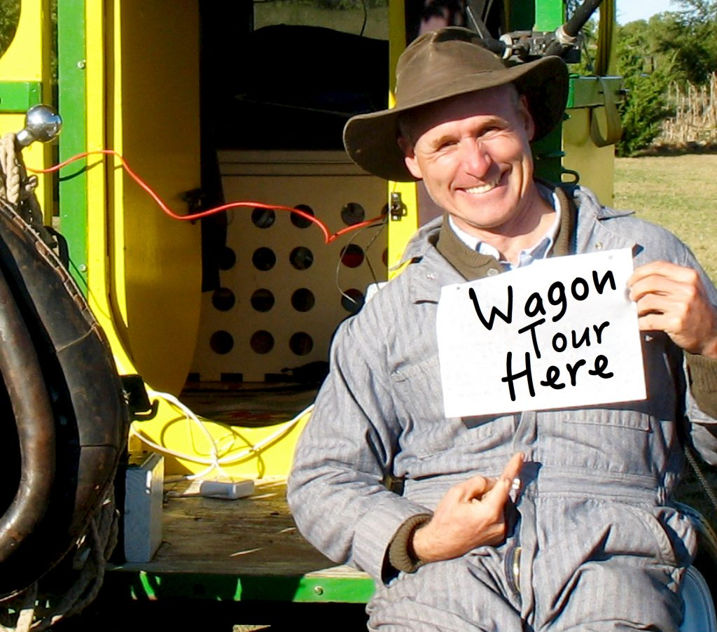 Bernie holds a sign in front of his wagon.